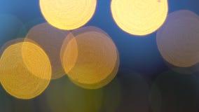 Gli effetti della luce dorati Defocused dei cerchi, sottraggono il fondo vago del boche di moto stock footage