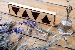Gli elementi - terra, fuoco, acqua, aria con la campana d'ottone e pacchi delle erbe secche su fondo di legno fotografia stock