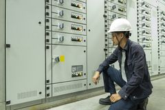 Gli elettricisti stanno controllando i pannelli di controllo elettrici in impianti industriali immagine stock libera da diritti
