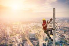 Gli elettricisti stanno scalando sui pali elettrici Immagine Stock
