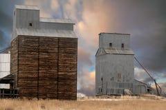 Gli elevatori di grano degli agricoltori uno hanno fatto di legno l'altro metallo Fotografia Stock Libera da Diritti