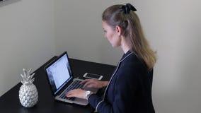 GLI EMIRATI ARABI UNITI, DUBAI - 15 GIUGNO 2017: Bella donna che utilizza il suo computer portatile nell'ufficio sullo scrittorio archivi video
