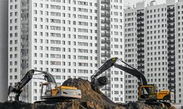 Gli escavatori lavorano alla terra su fondo di multi case del piano Fotografia Stock Libera da Diritti
