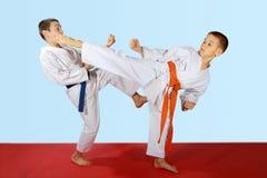 Gli esercizi accoppiati hanno eseguito dagli atleti con la cinghia blu ed arancio Fotografie Stock Libere da Diritti