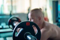 Gli esercizi con un bilanciere nella palestra, mettono in mostra il forte modello maschio fotografie stock libere da diritti
