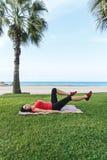 Gli esercizi di sport di allenamento della donna occupano all'aperto sulla spiaggia Immagine Stock