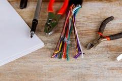 Gli estrattori dell'isolamento hanno messo delle pinze elettriche dei cavi sul concetto blu dell'elettricità del fondo Fotografie Stock Libere da Diritti