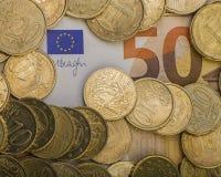 Gli euro centesimi delle monete sono su una fattura di carta di cinquanta euro Euro soldi Fotografie Stock Libere da Diritti