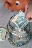 Gli euro di risparmio in vetro possono mentre orologi del maiale della banca Fotografia Stock Libera da Diritti