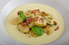 Gli gnocchi degli spinaci con la salsa del parmigiano hanno completato con bacon immagini stock