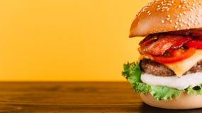 Gli hamburger appetitosi succosi luminosi con i tagli, formaggio, hanno marinato i cetrioli, i pomodori ed il bacon Immagini Stock