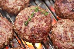 Gli hamburger crudi sul barbecue del bbq cuociono con fuoco Fotografie Stock