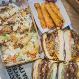 Gli hamburger della carne, l'insalata di Caesar ed i bastoni del formaggio affettati primo piano si trovano su un vassoio in un c immagini stock libere da diritti