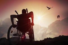 Gli handicappati handicappati equipaggiano hanno una speranza Sta sedendosi sulla sedia a rotelle e sta allungando le mani al tra fotografia stock libera da diritti