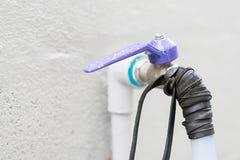 Gli idraulici risolvono l'acqua che cola dall'acqua di rubinetto facendo uso di un elastico intorno al rubinetto I problemi di pe Fotografie Stock Libere da Diritti