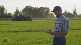 Gli impianti dell'agricoltore sul campo, utilizzano una compressa digitale video d archivio