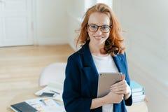 Gli impianti femminili piacevoli nella propria società, ha espressione facciale positiva, i capelli rossi lussuosi, impianti con  fotografia stock