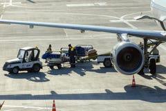 Gli impiegati caricano il bagaglio nel compartimento di bagagli degli aerei Immagini Stock