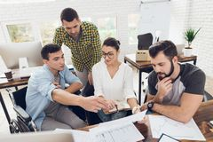 Gli impiegati di concetto e una persona in una sedia a rotelle discutono lavorare gli argomenti Funzionano in un ufficio luminoso fotografia stock