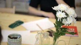 Gli impiegati di concetto sono venuto al comitato e si sono seduti alla tavola con i fiori stock footage