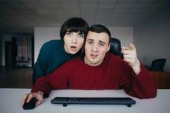 Gli impiegati di concetto sorpresi della gente lo hanno percepito emozionalmente che avete visto sullo schermo di computer ai pre Fotografie Stock Libere da Diritti