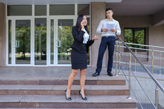 Gli imprenditori, ragazza sveglia utilizza il telefono ed il ragazzo porta la cartella Fotografia Stock