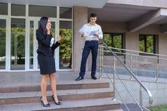 Gli imprenditori, ragazza sveglia utilizza il telefono ed il ragazzo porta la cartella Immagini Stock Libere da Diritti