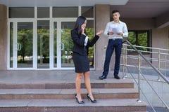 Gli imprenditori, ragazza sveglia utilizza il telefono ed il ragazzo porta la cartella Immagine Stock