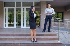 Gli imprenditori, ragazza sveglia utilizza il telefono ed il ragazzo porta la cartella Fotografie Stock Libere da Diritti