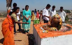 Gli indù eseguono il abhishekam a signore Shiva, statua di pietra, all'aperto Fotografie Stock Libere da Diritti