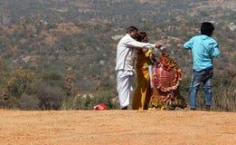 Gli indù eseguono il abhishekam a signore Shiva, statua di pietra, all'aperto Immagini Stock Libere da Diritti