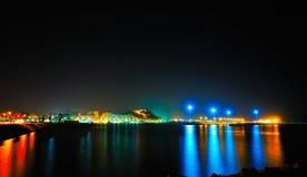 Gli indicatori luminosi di una città mediterranea entro la notte Immagini Stock