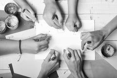 Gli indicatori in mani maschii e femminili attingono il Libro Bianco in bianco, copiano lo spazio Tavola di legno degli artisti c immagini stock libere da diritti