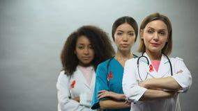 Gli infermieri femminili seri con i nastri e le mani rossi hanno attraversato, concetto di consapevolezza dell'AIDS stock footage