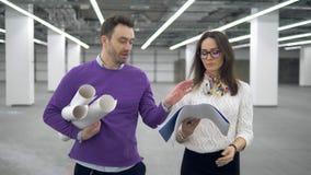 Gli ingegneri camminano in una stanza e discutono un programma di lavoro, tenente i modelli in mani video d archivio