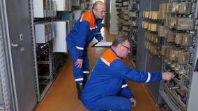 Gli ingegneri invecchiati mezzo controllano gli strumenti in gabinetti di potere della rete stock footage