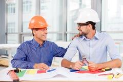 Gli ingegneri maschii allegri sono discutere Immagine Stock