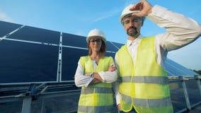 Gli ingegneri sorridenti dell'energetica stanno stando accanto ad una batteria solare e ad esaminare la macchina fotografica Conc video d archivio