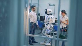 Gli ingegneri verificano i movimenti del ` s del robot, guardante lo tornitura stock footage