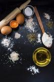 Gli ingredienti della pasta sul nero slates con olio d'oliva fotografia stock libera da diritti