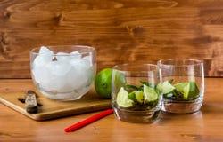Gli ingredienti ed il ghiaccio del taglio per un cocktail in un vetro sulla linguetta Immagini Stock