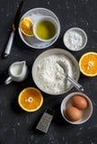 Gli ingredienti per la fabbricazione del dolce arancio con farina petrolio- verde oliva, uova, olio d'oliva, hanno spolverizzato  immagini stock libere da diritti