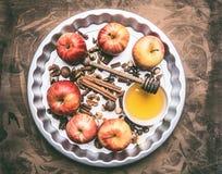 Gli ingredienti per le mele di cottura con miele ed i dadi, cannella e condimenti, hanno affettato le mele con il riempimento su  fotografie stock libere da diritti