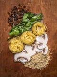 Gli ingredienti per pasta che cucina le linee delle noci tagliate funghi dell'uva passa delle erbe hanno presentato un tagliere s Fotografia Stock