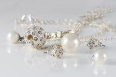 Gli insiemi dei gioielli del primo piano degli orecchini e dei pendenti d'argento fissati su acrilico sorgono su fondo grigio Immagine Stock