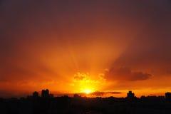 Gli insiemi del sole sopra la città Fotografie Stock Libere da Diritti