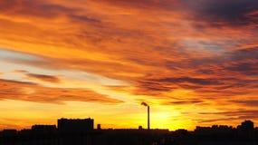 Gli insiemi del sole sopra la città Immagine Stock