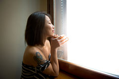 Gli occhi asiatici di fine della donna ritiene positivi con la tazza arancio Fotografia Stock Libera da Diritti