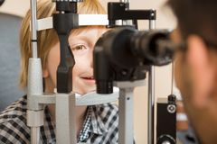 Gli occhi del ragazzo che sono esaminati secondo la lampada a fessura Immagine Stock Libera da Diritti