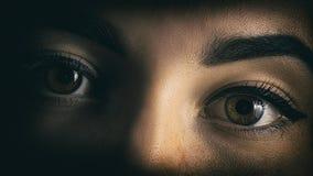 Gli occhi della ragazza chiudono il ritratto dell'orrore dalle ombre immagine stock